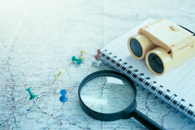 Concepto de viaje con lupa, marcadores en el mapa