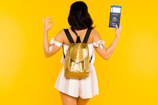 Concepto de viaje. mujer asiática joven que sostiene el pasaporte con boletos de pie hacia atrás con mochila muestra signo de ok