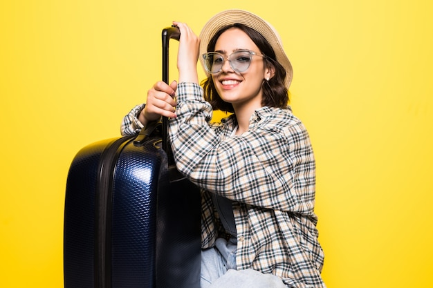 Concepto de viaje. mujer turista feliz con sombrero y gafas de sol listo para viajar con maleta y pasaporte aislado.