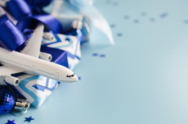 Concepto de viaje de navidad o año nuevo. avión de juguete con pasaportes y cajas de regalo sobre fondo azul.