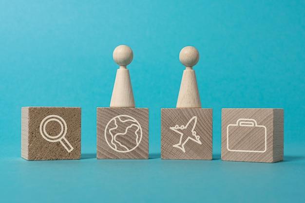 Concepto de viaje o plan de viaje de vacaciones figuras y bloques de madera con iconos sobre fondo azul.