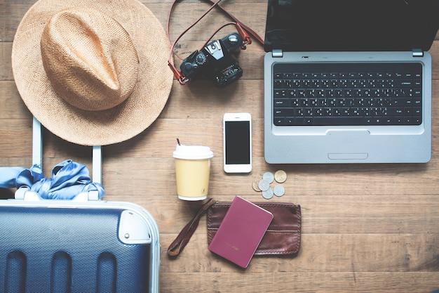 Concepto de viaje ordenador portátil en la mesa con artículos de viajero y teléfono inteligente