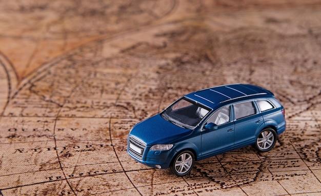 Concepto de viaje - pequeño coche de juguete deportivo azul en el mapa antiguo. copie el espacio.