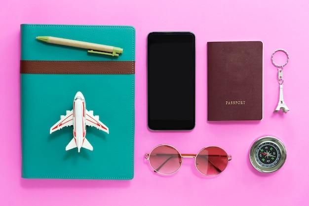 Concepto de viaje primer plano de móvil, pasaporte, brújula, gafas de sol y cuaderno en bac rosa