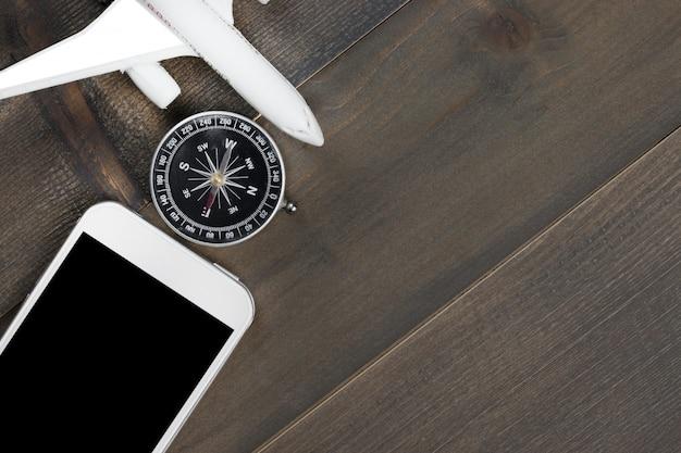 Concepto de viaje: teléfono, brújula y avión simulado sobre fondo de madera