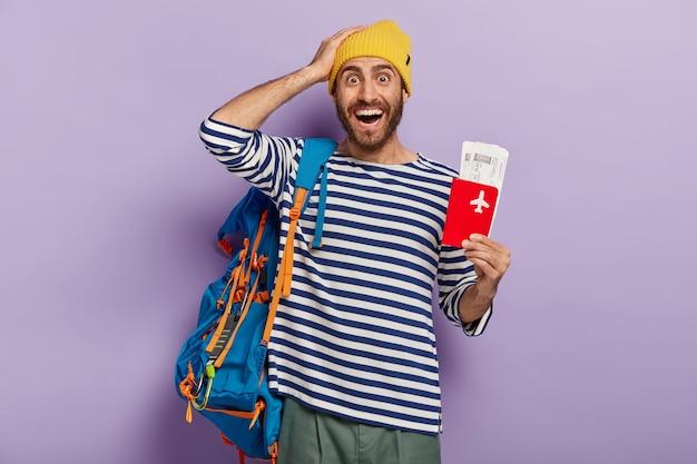 Concepto de viaje. turista hombre encantado se regocija viaje durante las vacaciones de verano posa con billete de viaje y documentos organiza todo para viajar lleva mochila. el mochilero ha esperado durante mucho tiempo el viaje