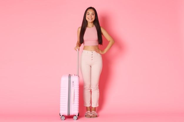 Concepto de viaje, vacaciones y vacaciones. longitud total de alegre niña asiática sonriente en ropa de verano lista para ir al extranjero, sosteniendo la maleta sobre la pared rosa
