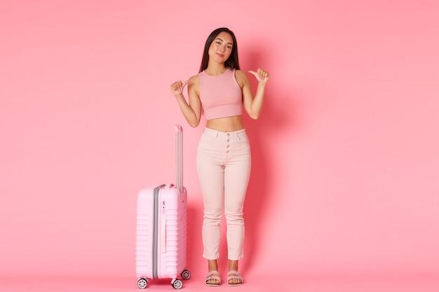 Concepto de viaje, vacaciones y vacaciones. longitud total de una chica asiática guapa con ropa de verano llena de bolsas para ir al extranjero, señalando a sí misma descarada, viaje perfecto planeado, sujeta la maleta.
