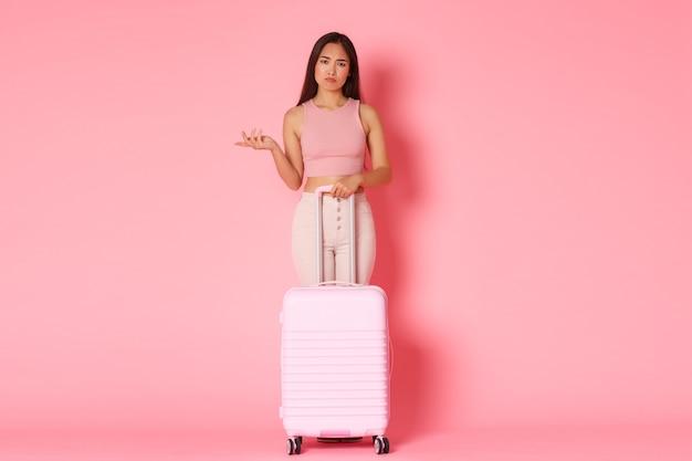 Concepto de viaje, vacaciones y vacaciones. longitud total de una elegante chica asiática frustrada y molesta en ropa de verano, levantando la mano confundida, de pie con la maleta