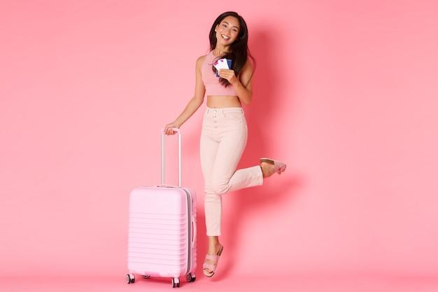 Concepto de viaje, vacaciones y vacaciones. longitud total de feliz niña asiática sonriente, turista con boletos de avión y pasaporte, saltando de la emoción antes del viaje, sosteniendo la maleta, pared rosa