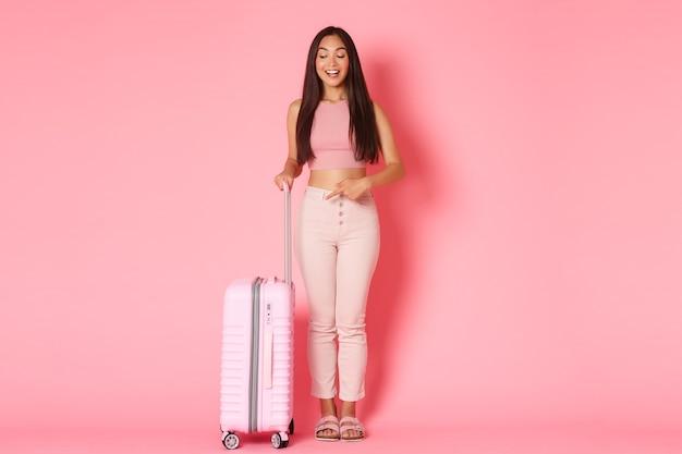 Concepto de viaje, vacaciones y vacaciones. longitud total de pensativa y complacida turista asiática, alabando una gran maleta nueva, señalando con el dedo su mala y sonriente pared rosada encantada