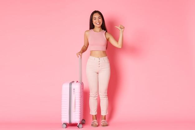Concepto de viaje, vacaciones y vacaciones. longitud total de una turista asiática descarada y feliz de pie sobre una pared rosa con una maleta y apuntando a sí misma, explorar países