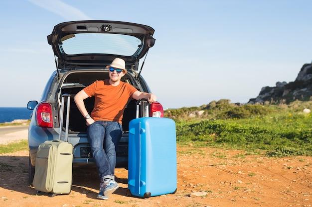 Concepto de viaje, vacaciones, viaje de verano y personas: el hombre se va de vacaciones, maletas en el maletero de un automóvil.