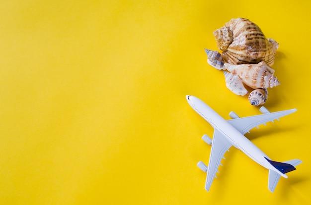 Concepto de viaje de verano. avión decorativo y conchas marinas sobre fondo amarillo.