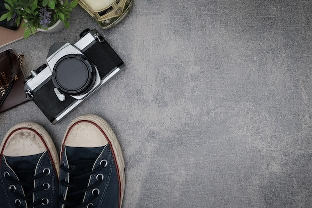 Concepto de viaje de vista superior con películas de cámara retro, otros artículos sobre fondo de cemento gris