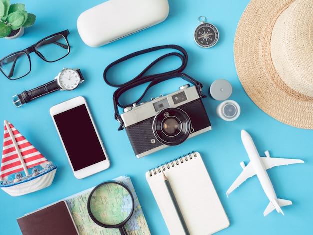 Concepto de viaje de la vista superior con películas de cámara retro, teléfono, mapa, pasaporte, brújula y atuendo de viajero en superficie azul, elementos turísticos esenciales, efecto de tono vintage