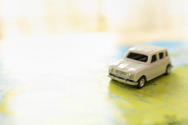Concepto de viajes y transporte. primer plano de un mini coche de juguete blanco en el mapa del mundo con espacio de copia.