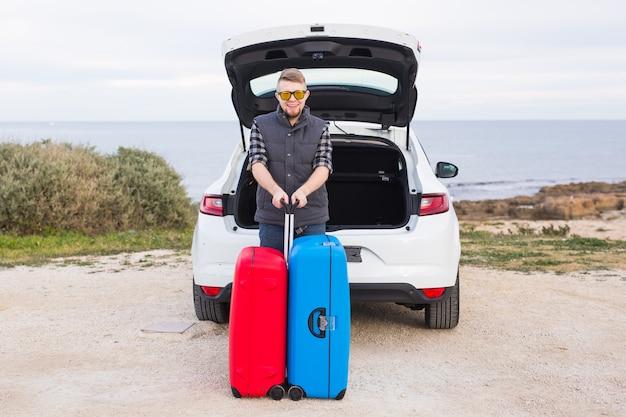 Concepto de viajes, turismo y personas - hombre feliz con gafas de pie con maletas sobre la superficie de la naturaleza cerca del coche.