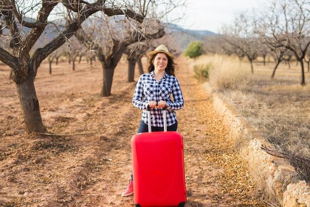 Concepto de viajes, turismo y personas - mujer joven feliz que va a viajar con maleta roja y