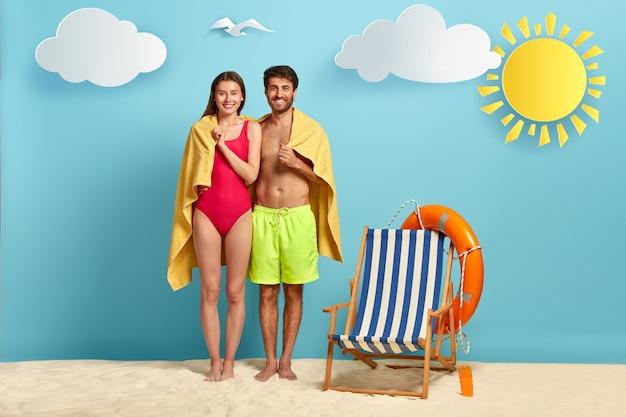 Concepto de viajes y verano. refugio de pareja alegre bajo una toalla de playa suave, vestida con traje de baño