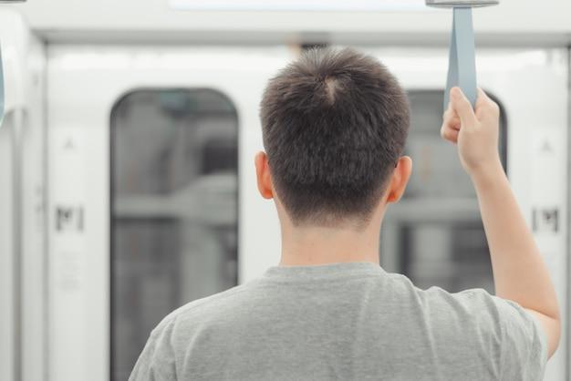 Concepto de vida en la ciudad, mano masculina con un asa en bucle en transporte público urbano