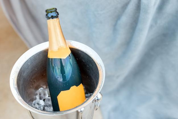 Concepto de vida de lujo con botella de champagne en el cubo de hielo. tema de celebración con champán bodegón.
