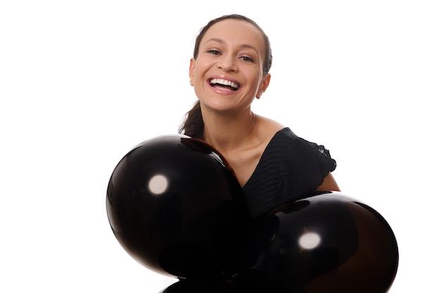 Concepto de viernes negro con una atractiva mujer bonita de raza mixta con hermosa sonrisa con dientes, vestida de negro mira a los soportes de la cámara con globos de aire negros sobre fondo blanco, espacio de copia.