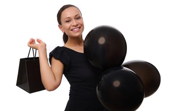 Concepto de viernes negro con atractiva mujer de raza mixta con hermosa sonrisa con dientes, vestida de negro mira a los soportes de la cámara con globos de aire negros y bolsa de compras, fondo blanco, espacio de copia.