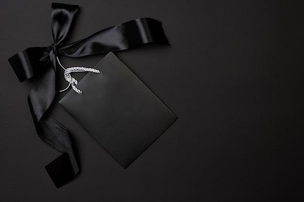 Concepto de viernes negro bolsa de compras negra en soporte de tela con gran cinta negra sobre fondo oscuro