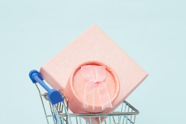 Concepto de viernes negro, cajas de regalo con carrito de compras sobre fondo azul pastel, espacio de copia