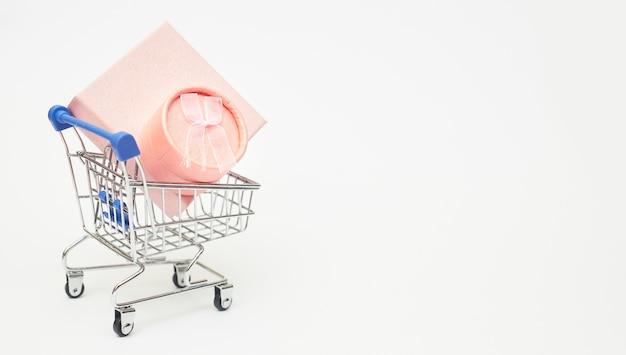 Concepto de viernes negro, cajas de regalo con carrito de compras sobre fondo blanco, espacio de copia