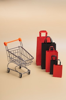 Concepto de viernes negro, maqueta de bolsas de papel negras y rojas con carro sobre fondo de color. venta de viernes negro. foto vertical