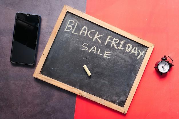 Concepto de viernes negro con tablero negro y reloj sobre fondo de color,