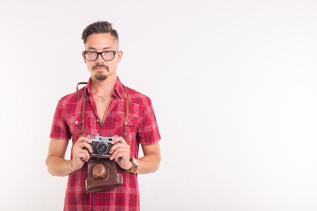 Concepto vintage, fotógrafo y personas - hombre guapo con cámara retro sobre superficie blanca con