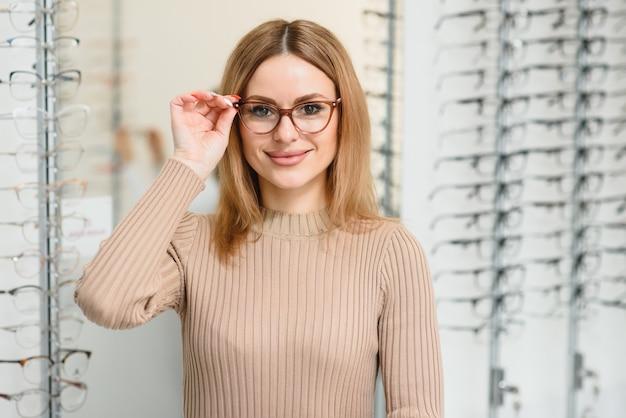 Concepto de visión y visión - mujer de negocios joven que elige gafas en la tienda de óptica