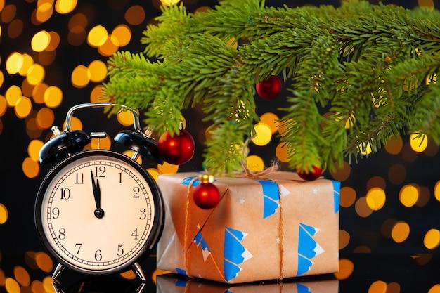 Concepto de víspera de año nuevo con reloj despertador contra fondo borroso garland