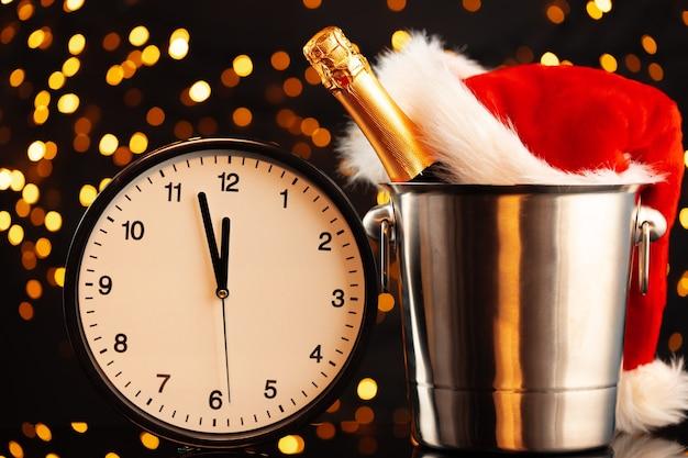 Concepto de víspera de año nuevo con reloj despertador contra guirnalda borrosa