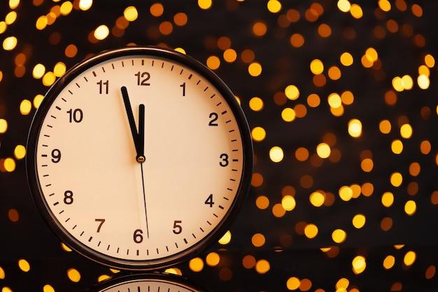 Concepto de víspera de año nuevo con reloj despertador en guirnalda borrosa