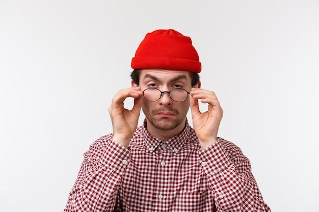 Concepto de vista, salud y óptica. retrato de primer plano de gracioso lindo hombre barbudo caucásico probándose lentes nuevos recetados, no puedo ver nada, entrecerrando los ojos para mirar al médico, en una pared blanca