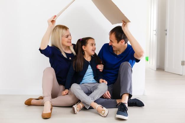 Concepto de vivienda a una familia joven. madre, padre e hijo en casa nueva con techo.