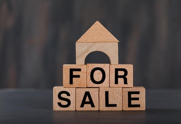 Concepto de vivienda en venta con cubos de madera, casa de madera gris.