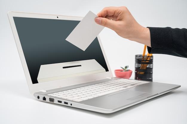 Concepto de votación en línea con un hombre con una boleta en la mano poniendo una boleta hacia el monitor de la computadora.
