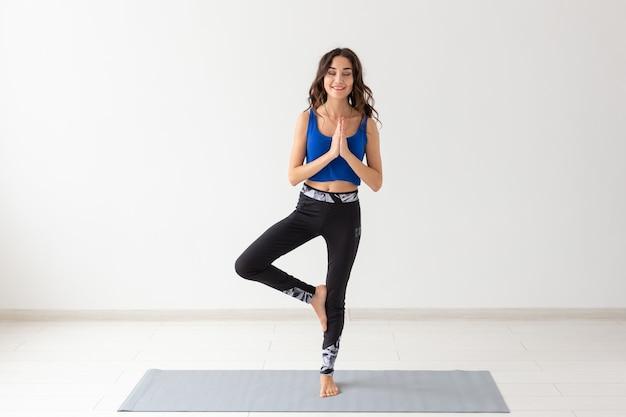 Concepto de yoga, deporte, relax y personas - mujer joven practicando yoga en el interior