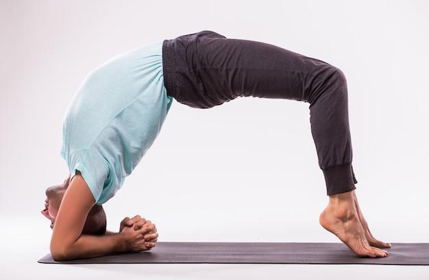 Concepto de yoga. hombre guapo haciendo ejercicio de yoga aislado sobre un fondo blanco.