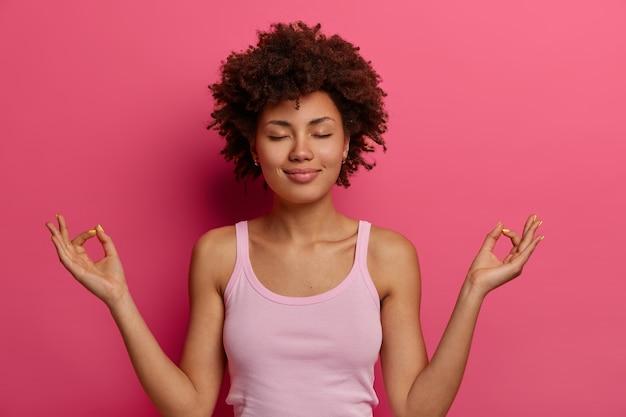 Concepto de yoga y meditación. relajada y satisfecha mujer de piel oscura toma las manos en un gesto de mudra, se siente en paz después de un duro día, mantiene los ojos cerrados, controla sus sentimientos, se para en posición de loto.