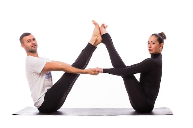 Concepto de yoga en pareja. pareja joven sana en posición de yoga sobre fondo blanco.