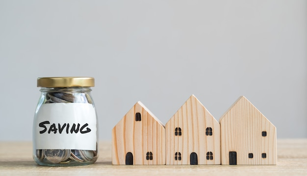 Conceptos de ahorro de dinero. modelos de casas de madera con monedas en botella y etiqueta de ahorro que significa ahorrar dinero para comprar una casa, refinanciar, invertir o financiar en una mesa de madera con espacio de copia.