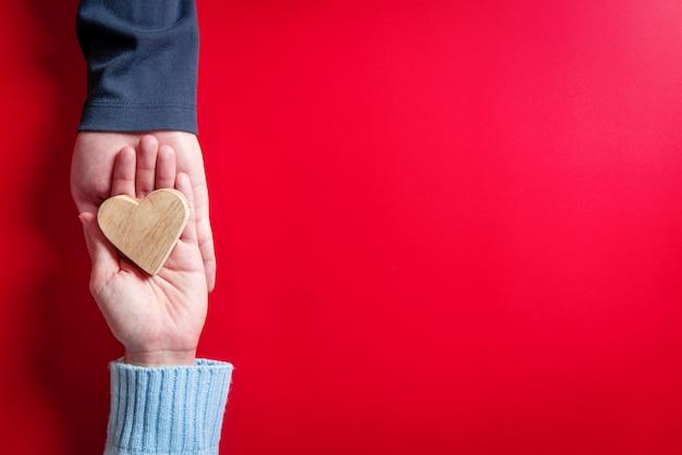 Conceptos de amor, pareja de enamorados con el corazón en las manos en rojo