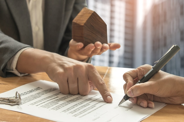 Conceptos de comercio de bienes raíces, corredores de casas y compradores que firman un contrato de venta.