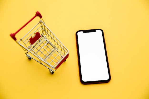Conceptos de compras en línea con carro de maquetas y teléfono inteligente en amarillo